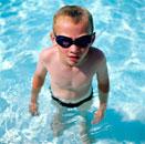 Boy in swimming goggles in swimming pool