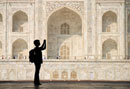 Silhouette of woman with rucksack photographing the Taj Maha