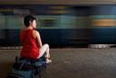 Backpacker sitting on rucksack in train station,Blurred Mo