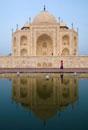 Tourist walking by the Taj Mahal at dusk