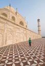 Woman walking beneath the Taj Mahal on tiled ground