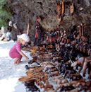 Child looking at wooden souvenirs for sale on the beach