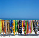 Colorful sarongs hanging over white sand beach