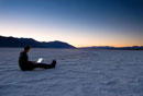 Man using laptop on the salt pans at dawn