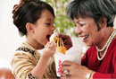 Grandmother and Granddaughter Sharing Chinese Food