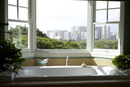 Modern bathtub near window with view of Hawaiian downtown city