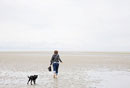 Woman and Dog Walking on Beach
