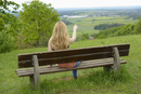 Rear View of Young Woman Sitting on Bench and Pointing into the Distance, Germany