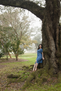 A woman in a blue dress leaning against a tree in Louisianna