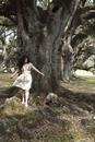 A woman walking near some oak trees, the southern USA