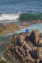 Sport fisherman sitting on rocks as waves wash ashore in the Baixo Alentejo region of Portugal. A popular pastime in Portugal.