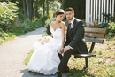 Portrait of Bride and Groom sitting on wooden bench outdoors, Ontario, Canada