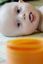 Close-up of baby with down syndrome looking at a slinky that he uses for physical therapy.