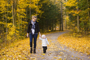 Mother walking on Country Road with Baby Daughter in Autumn, Scanlon Creek Conservation Area, Ontario, Canada