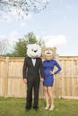 Portrait of couple standing in backyard dressed in formal attire, covering faces wearing costume bear heads, Canada