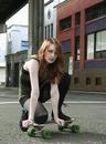 Young Woman Kneeling on Skateboard Outdoors, Portland, Oregon, USA