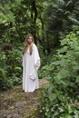 Woman with blond hair wearing long, white gown, standing on path in the woods, USA