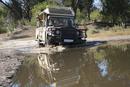 Africa, Botswana, Okavango Delta,Vehicle crossing waterhole