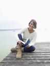 Germany, Munich, Mature woman sitting on jetty near lake holding book, smiling, portrait