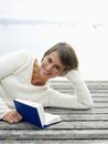 Germany, Munich, Mature woman lying on jetty near lake reading book, smiling, portrait