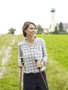 Germany, Munich, Mature woman nordic walking, smiling