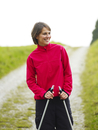 Germany, Munich, Mature woman with nordic walking pole, smiling