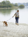 Germany, Munich, Mature woman near lake with dog, smiling