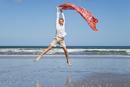 New Zealand, Mature woman jumping at Ninety Mile Beach