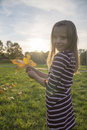 Little girl with autumn leaves in her hands standing on a meadow