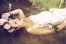 Portrait of young woman wearing wedding dress and flower crown lying in the water with closed eyes