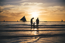 Philippines, Boracay, family with one child at seashore by sunset