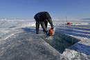 Russia, Lake Baikal, man opening an ice hole with a motor saw for ice diving