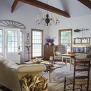 LIVING ROOM : Country style, neutral monochromatic, rag rug, doorway with architectural element above, long  windows, wing chair