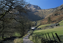 View along road to farm, with Harrison Stickle towering above, Great Langdale, Lake District National Park, Cumbria, England, Un