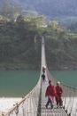 Local people crossing the 160m long suspension bridge, Trisuli Center, Bandare village, Trisuli Valley, Nepal, Asia
