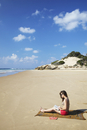 Woman reading on beach, Tofo, Inhambane, Mozambique, Africa