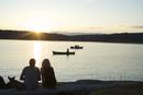 Silhouette of couple with dog watching sunset at Lisabeula Beach, Vashon Island, Washington State, United States of America, Nor