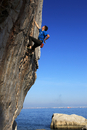 A climber tackles a difficult route on the limestone sea cliffs of Akyalar, with the city of Antayla in the distance, Anatolia,