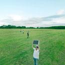 モニターを手に草原をゆく若者達