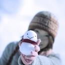雪ダルマを持って微笑む女性