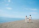 海辺を手をつないで歩く親子の後姿