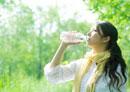 新緑の下で水を飲む若い女性