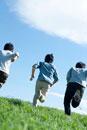 青空と草原を走る3人の若者たちの後姿