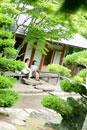 旅館の縁側に座り庭園を眺める2人のシニア女性