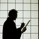 障子の前で俳句を書くシニア男性のシルエット
