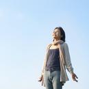 草原に立ち深呼吸をするシニア女性