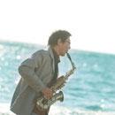 海辺でサックスを演奏するシニア男性