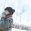 雪原の中で手袋をして暖まる女の子の横顔