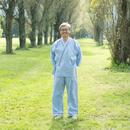 ポプラ並木で患者衣を着て微笑むシニア男性