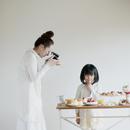 たくさんのお菓子の写真を撮る女性と女の子